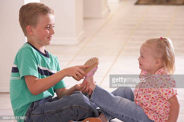 Brother (6-8) putting shoe on sister (1-3), sitting on floor