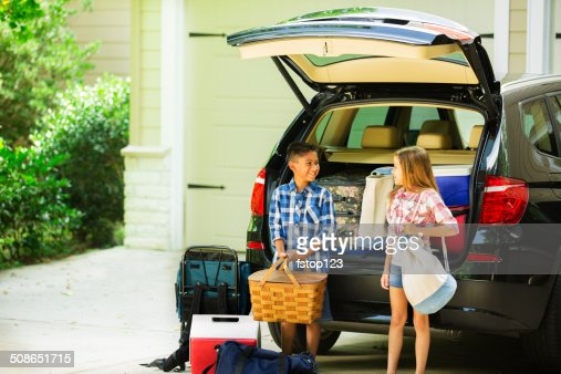 Brother, sister packing car to go on summer family vacation. : Stock Photo