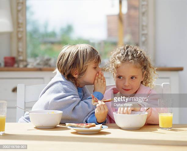 Brother whispering to sister (4-6) at breakfast table