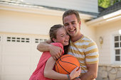 Brother with arm around sister holding basketball