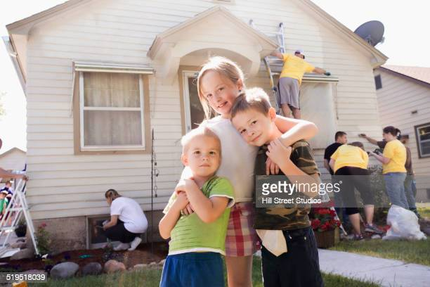 Brothers and sister hugging outside house