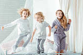 Small brothers and sister jumping on bed