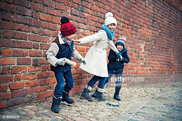 Brothers and sister playing near warsaw old town castle wall