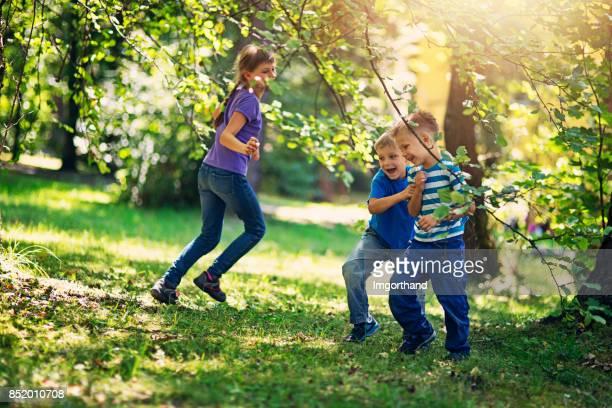 Brüder und Schwester spielen im Garten