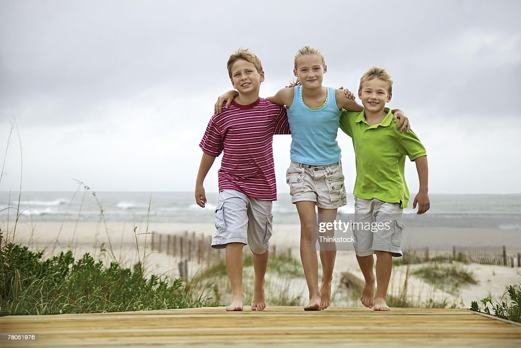 Brothers and sister walking on boardwalk
