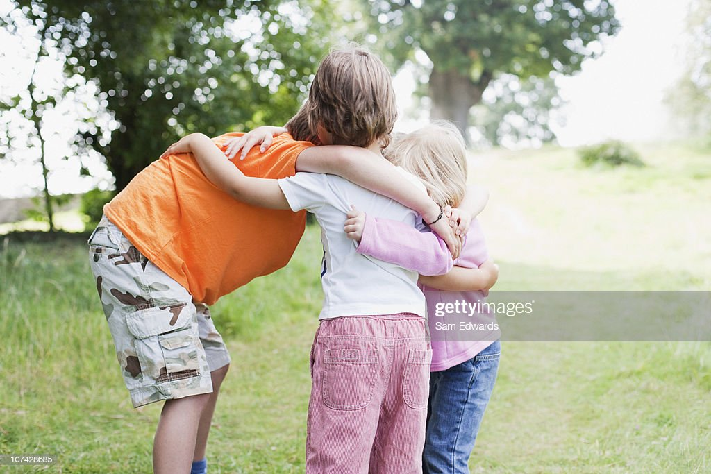 Brothers and sisters huddling together outdoors : Stock Photo