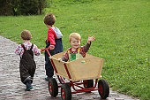 Girl and boy pulling their brother sitting in a handcart