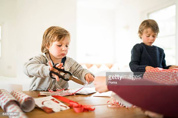 Brothers are preparing Christmas gifts at table