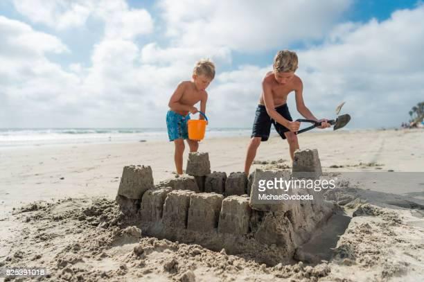 Château de sable de frères à l'édifice de la plage A