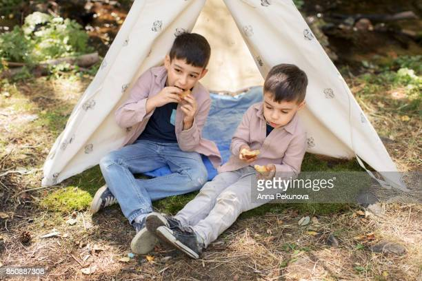 Brothers eating muffins outdoors