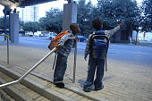 Brothers Elliott and Ashton WIlliams stand outside the Austin Convention Center on Wednesday waiting for a school bus to take them to elementary...