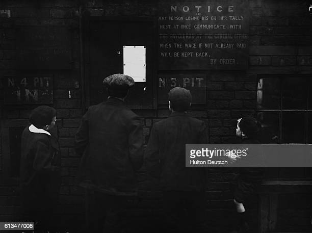 Brothers employed in a coal mine gather to read a notice posted on a bulletin board during a labor strike scare