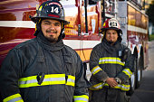 Firefighter brothers standing in front of rescue fire truck with copy-space.