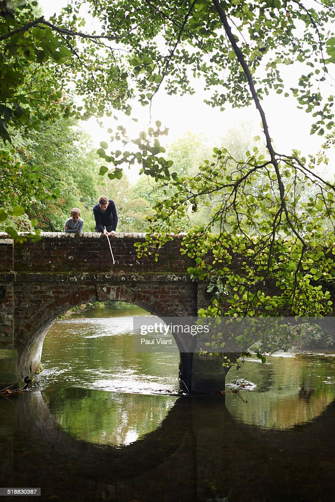 Brothers fishing off stone bridge