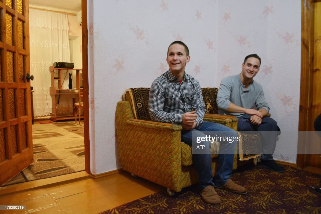 Brothers Genya (R) and Dima Onoprienko pose for a photograph in their home in Gzhankoy, Crimea, on March 11, 2013. The Onoprienko family is split down the middle on whether Crimea should become part of Russia or stay with Ukraine, reflecting deep divisions between even blood relatives ahead of the March 16 referendum on the region's future. Dima, 17 -- a computing student who loves the Beatles, 'Breaking Bad' and Western sportswear -- and his mother Olga, a kindergarten teacher, are both desperate for Crimea to remain an autonomous region of Ukraine. But Dima's bodybuilding brother Zhenya, 20, and taxi driver father Sasha believe that only closer ties with President Vladimir Putin's Russia can bring Crimea the jobs and stability it desperately needs.