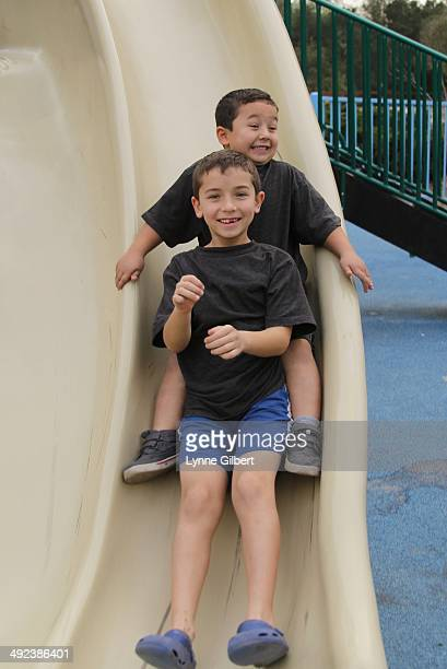 Brothers going down a slide at the park