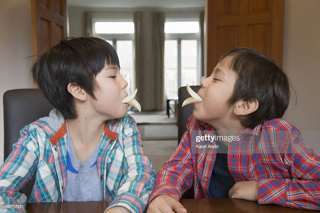 Brothers imitating bird beak with crisps : Stock Photo