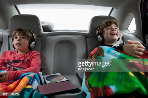 Brothers in back seat of car, wearing headphones
