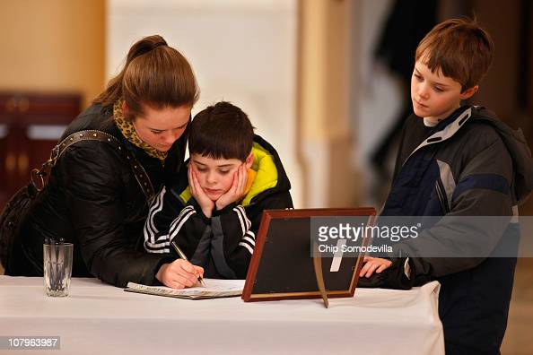Brothers Isaac Smith and Silas Smith look on as their sister Blanche Smith signs condolence and wellwishes books for the victims of Saturday's mass...