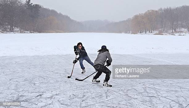 Brothers Jeff and Bryan Takahashi play some hockey on a cleared off patch of ice on the pond Toronto city councillor Sarah Doucette wants to bring...