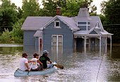 Brothers John Jerry and Ed Tharp canoe through the flooded streets of their town 09 July 1993 after the rising Mississippi River breached the town...