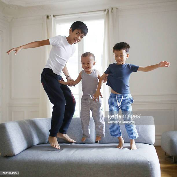 3 brothers jumping on a sofa