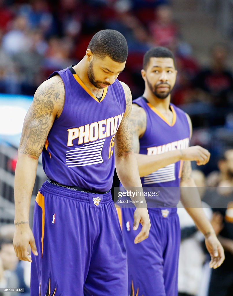 Brothers Marcus Morris and Markieff Morris of the Phoenix Suns walk onto the court at the start of their game against the Houston Rockets at the...