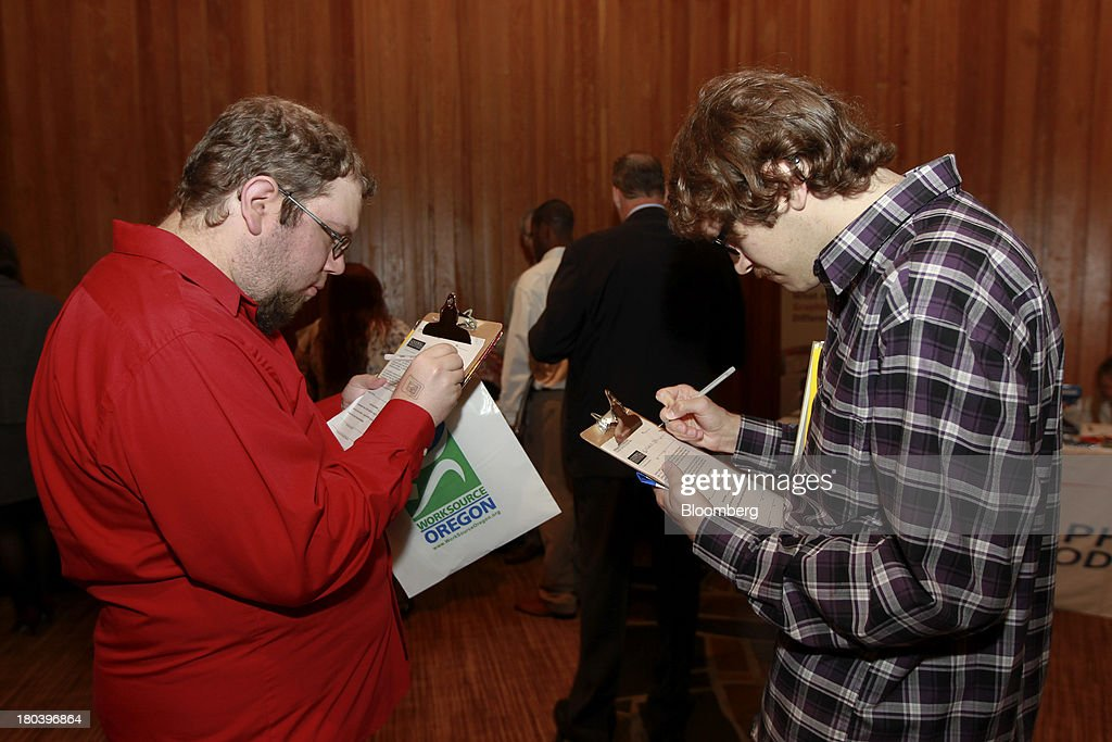 Brothers, Matt, right, and Evan Hilliard fill out applications for Goodwill Industries at the annual Maximum Connections job fair in Portland, Oregon, U.S., on Thursday, Sept. 12, 2013. Jobless claims in the U.S. declined last week to the lowest level since April 2006 as work on computer systems in two states caused those employment agencies to report fewer applications. Photographer: Natalie Behring/Bloomberg via Getty Images