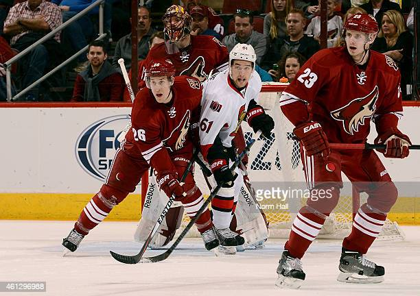 Brothers Michael Stone of the Arizona Coyotes and Mark Stone of the Ottawa Senators battle for position in front of the net during the first period...