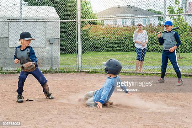 Brothers playing baseball, one sliding to the plate mom watching.