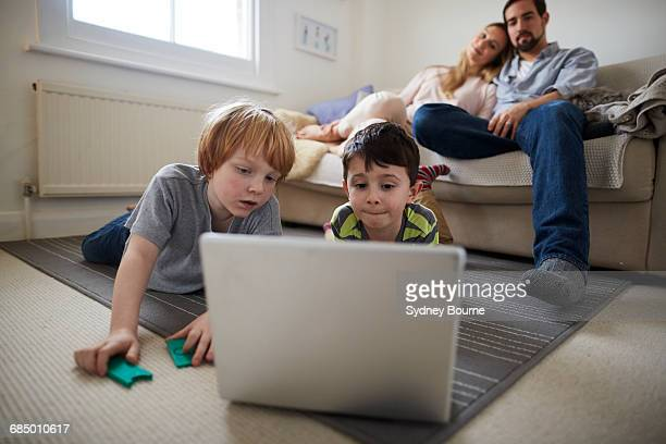 Brothers playing laptop game on room rug, parents on sofa