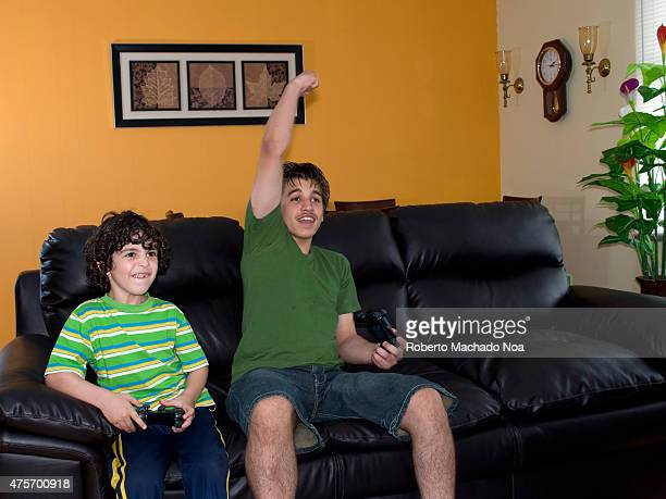 Brothers playing on a games console sitting on a black leather couch in the home Older brother raised his hand up in victory sign