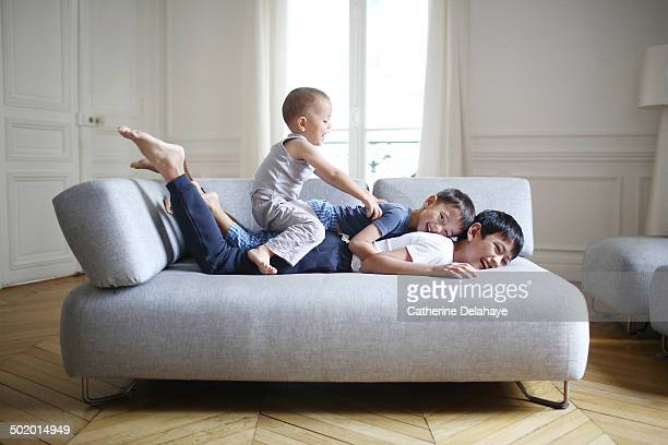 3 brothers playing on a sofa