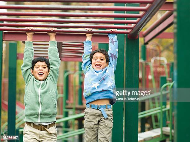 Brothers playing on monkey bars at playground.