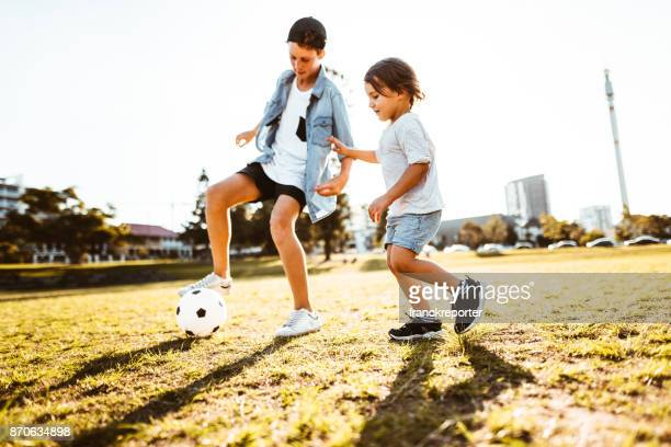 brothers playing soccer at the park