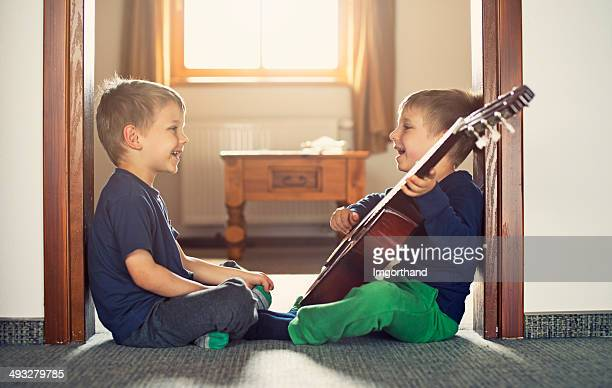 Brothers playing the guitar and singing
