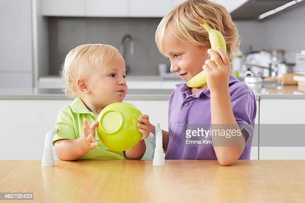 Brothers playing with bowl and banana at table