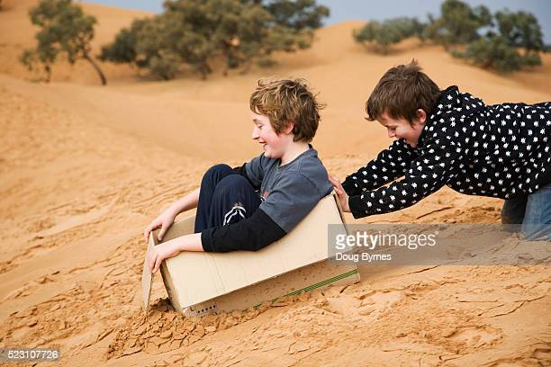 Brothers Playing with Cardboard Box on Sand Dunes