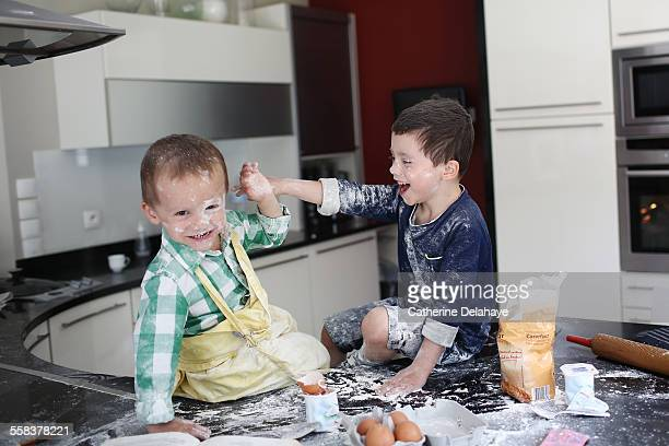 2 brothers playing with flour in the kitchen