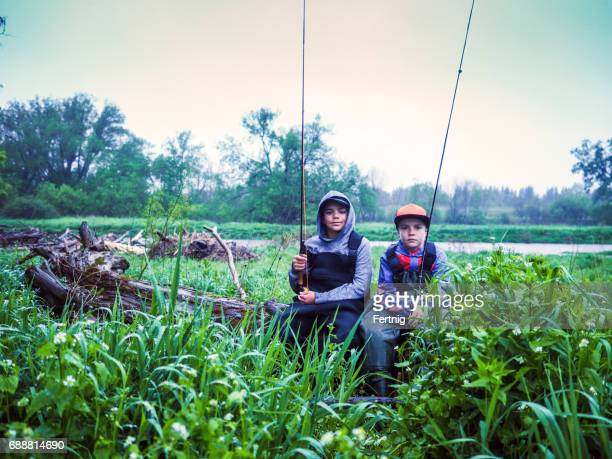 Brothers resting on a log while fly-fishing on a trout stream