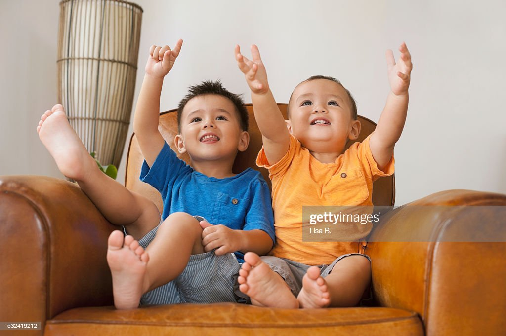 Brothers (6-11 months, 12-23 months) sitting on sofa