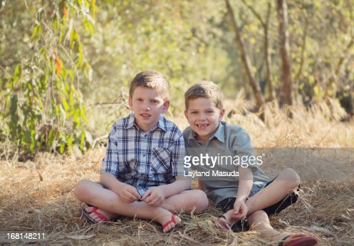 Brothers Sitting Outdoors In The Country