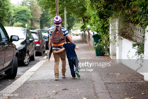 Brothers walking down the road arm in arm : Stock Photo