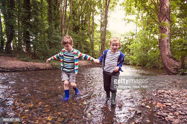 Brothers walking in a river
