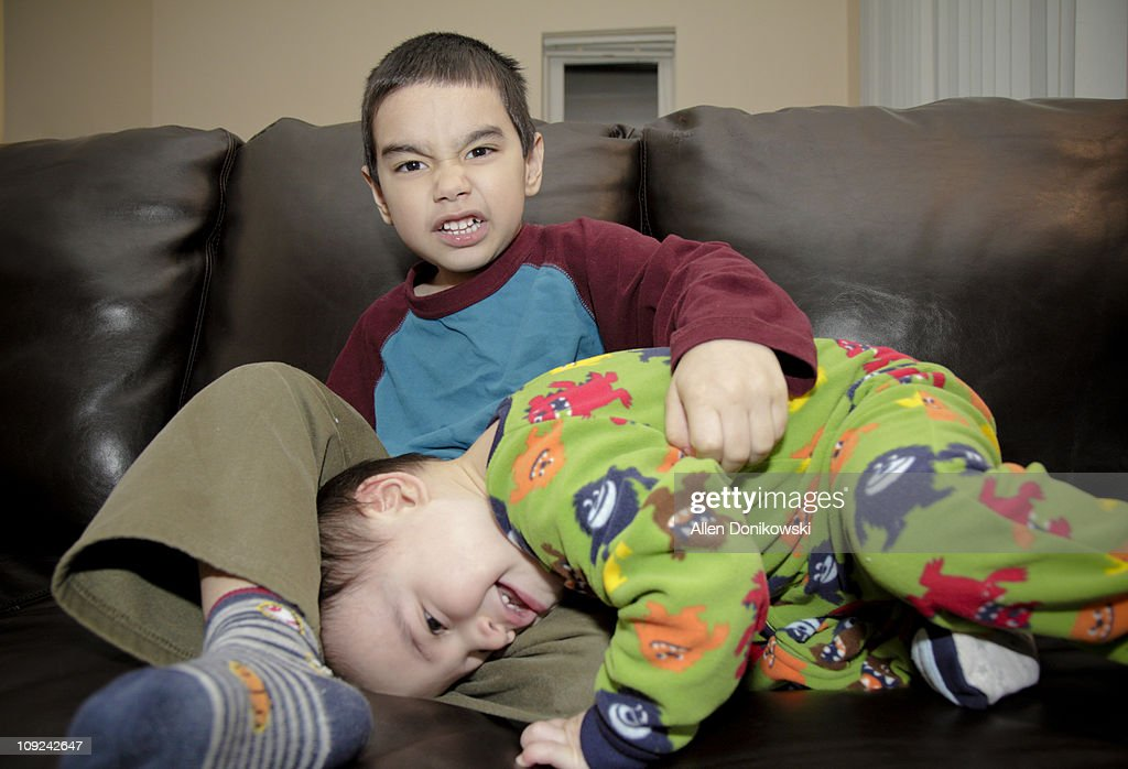 Brothers wrestling on the couch : Stock Photo