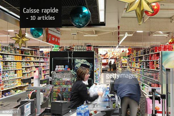 Brou 'Intermarche' supermarket Checker and customer at the fast checkout reserved for customers with less than ten items Christmas decorations on the...