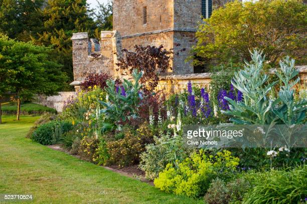 Broughton Castle, Oxfordshire: The Battlement Border in Summer with Cardoons and Blue Delphiniums -