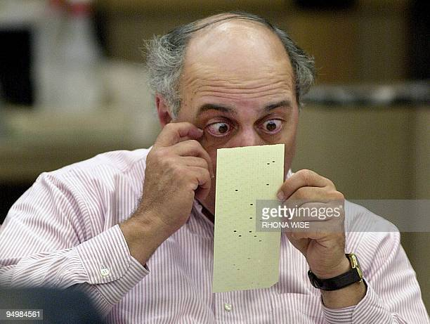 Broward County canvassing board member Judge Robert Rosenberg looks over a questionable ballot 25 November 2000 at the Broward County Courthouse in...