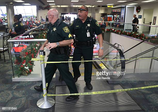 Broward County Sheriff officers exit from the escalator that takes people from the baggage area of Terminal 2 where yesterday a shooter killed five...
