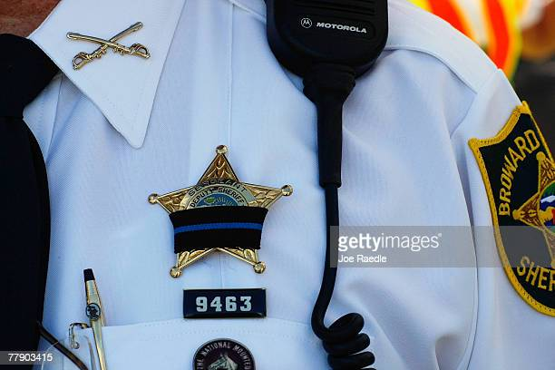 Broward Sheriff's Deputy wears a black ribbon on his badge as he honors Broward Sheriff's Deputy Paul Rein during his funeral at the Broward Center...